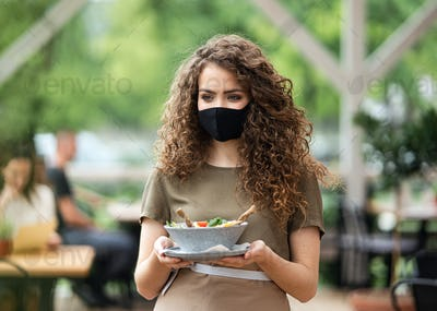 Waitress with face mask serving customers outdoors on terrace restaurant