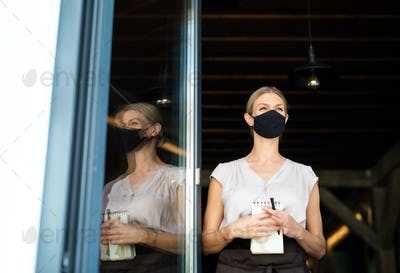Portrait of waitress with face mask standing at the door in restaurant