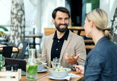 Happy couple sitting outdoors on terrace restaurant, talking