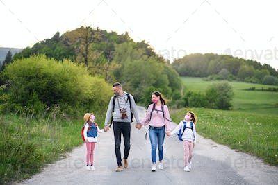 Family with two small daughters on trip outdoors in nature, wearing face masks
