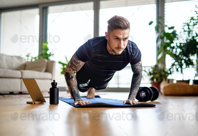 Front view portrait of man with tablet doing workout exercise indoors at home