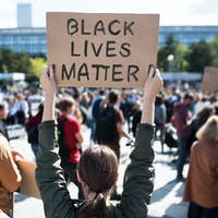Rear view of black lives matters protesters holding signs and marching outdoors in streets
