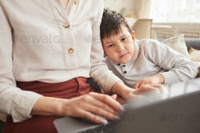 Cute Boy Looking at Laptop Screen while Mom Working at Home