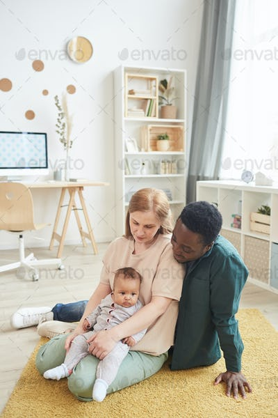 Happy Mixed Race Family Playing on Floor
