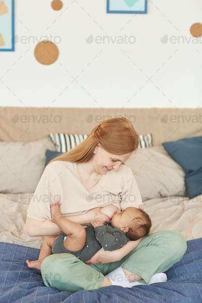 Mother Breastfeeding Baby on Bed