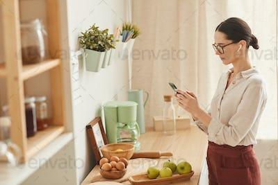 Elegant Woman Using Smartphone at Home