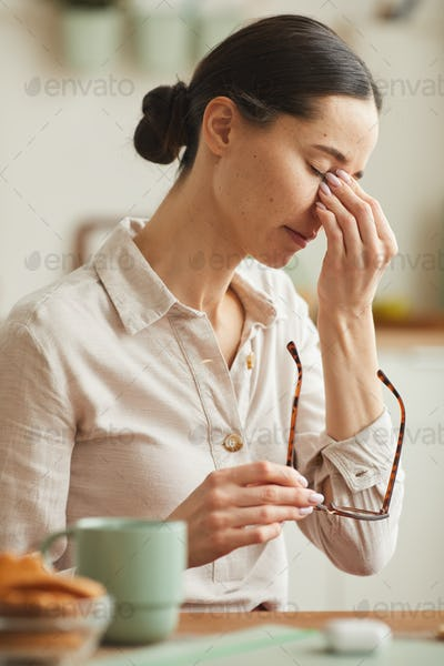 Stressed Young Woman Taking off Glasses