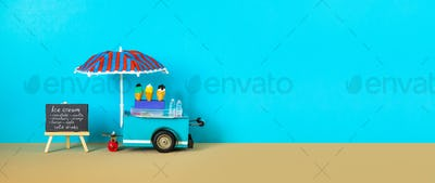 Ice cream toy cart with blue red umbrella. Assortment of ice cream menu black chalkboard.