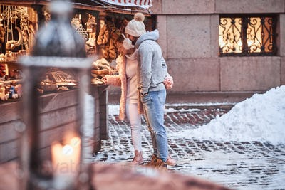 A happy young couple choosing the gift in a souvenir shop outdoors on a Christmas fair.