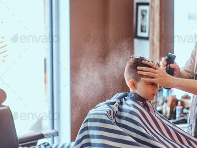 Small school boy is getting trendy haircut from expirienced barber at modern barbershop