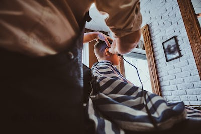 Cute little child is getting trendy haircut from barber at busy barbershop