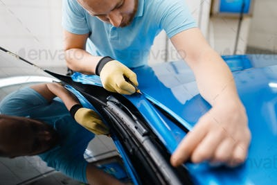 Car wrapping, man cuts protective foil or film