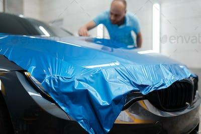 Car wrapping, man installs protective vinyl foil