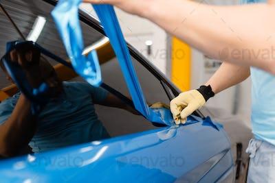 Mechanic hands installs car foil or film