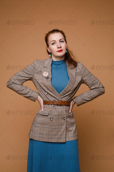 Model in dress and jacket with hands on waist looking at camera