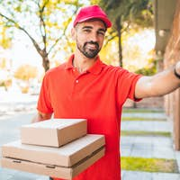Delivery man with pizza box ringing house doorbell..