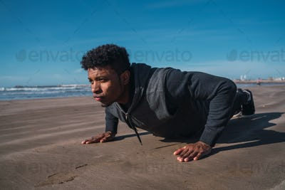 Athletic man doing push-ups at the beach.
