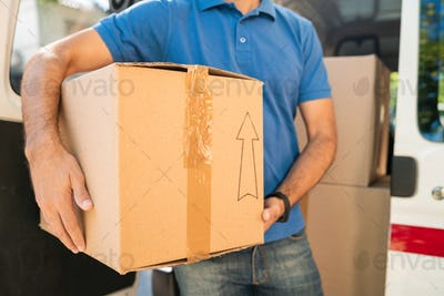 Delivery man unloading cardboard boxes from van.