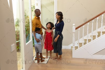 Mixed race couple and their young son and daughter standing in the hallway of their home