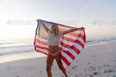 Caucasian woman holding and waving an US flag at the beach.