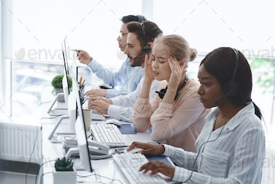 Technical support operator suffering from headache and her colleagues working with computers in