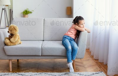 Girl Sitting Uninterested In Toys Looking At Window At Home
