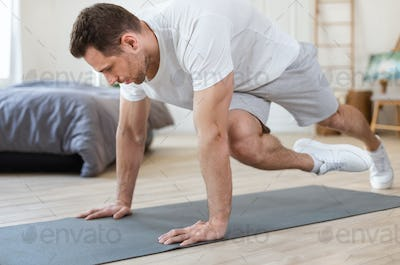 Sporty Man Training At Home Doing Running Plank Exercise