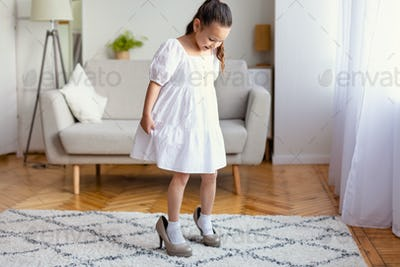 Little Girl Wearing Mom's High Heels Shoes Playing At Home