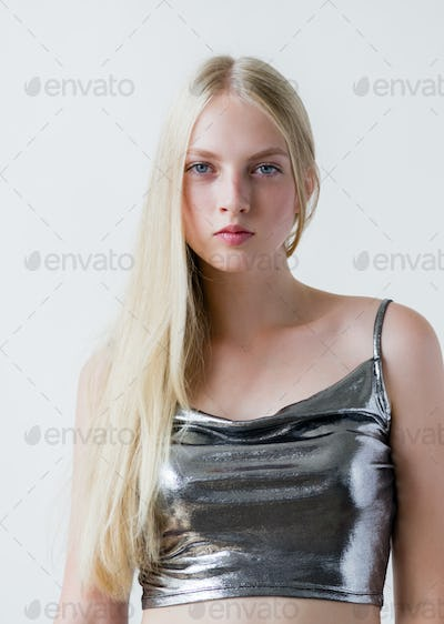Beautiful blonde woman girl with long blond hair smooth and beauty in silver wear