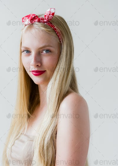 Beautiful pinup woman with long blonde hair natural on white background