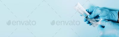 Medical concept banner with copy space. Hand in gloves holding syringe on blue background