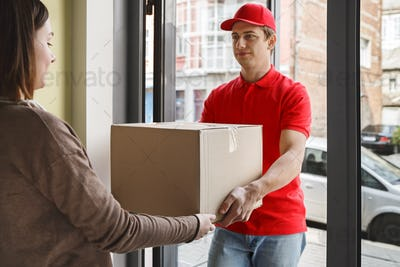 Purchase from online store and delivery. Girl takes cardboard box from courier