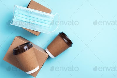 Craft paper cups with coffee to go and food box, lunch on blue background. Top view. Banner, copy