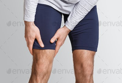 Muscle pain in athlete. Man in sportswear presses his hands to leg