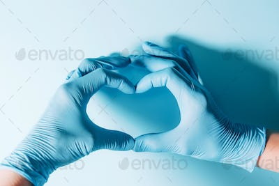 Figure heart built with hands in medical gloves on blue background. Copy space. National Doctors'