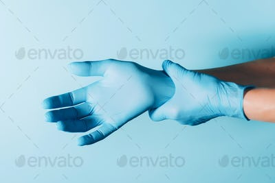 Doctor wears blue sterilized surgical gloves on blue background. Copy space. National Doctors'