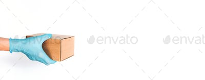 Home delivery, safe package, online order concept. Hand in medical glove gives craft box