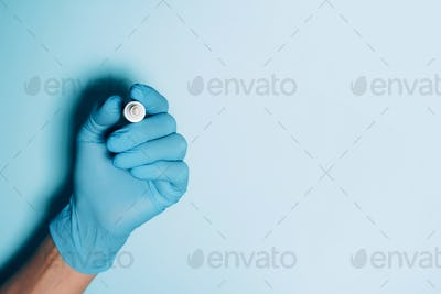 Doctor hand in medical glove and white pen on blue background. Copy space. Coronavirus, COVID-19