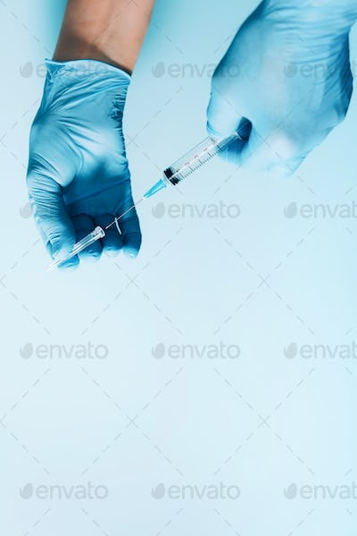 Hand in medical gloves holding syringe on blue background. Copy space. Injections and vaccination