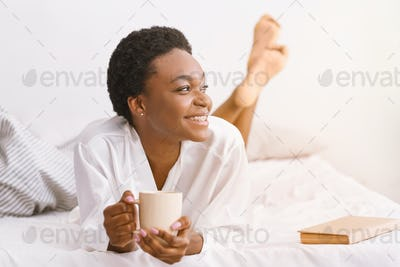 Good morning in comfortable bed. Smiling african american girl holding cup of coffee