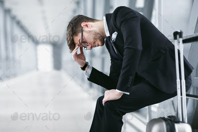 Sad urban business man sitting in airport