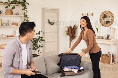 Joyful Travelers Couple Packing Suitcase For Vacation At Home