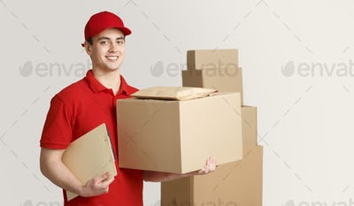 Courier and package in warehouse. Deliveryman holding box and tablet near stack of parcels