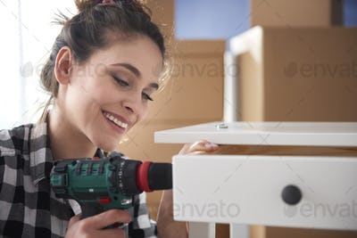 Close up of cheerful woman using electronic drill
