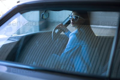 Fashion lady driving a car in a blue suit. Stylish girl sitting in the car at the wheel
