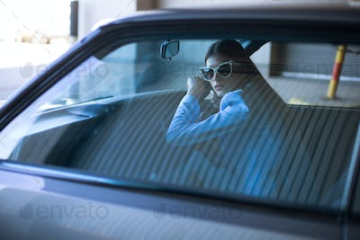 Fashion lady driving a car in a blue suit. Stylish girl sitting in the car at steering wheel