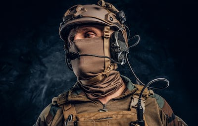 Close-up portrait. Private security service contractor in camouflage helmet with walkie-talkie.