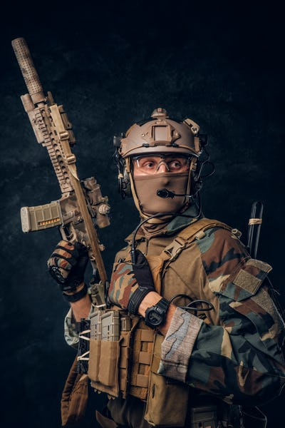 Elite unit, special forces soldier in camouflage uniform posing with assault rifle.