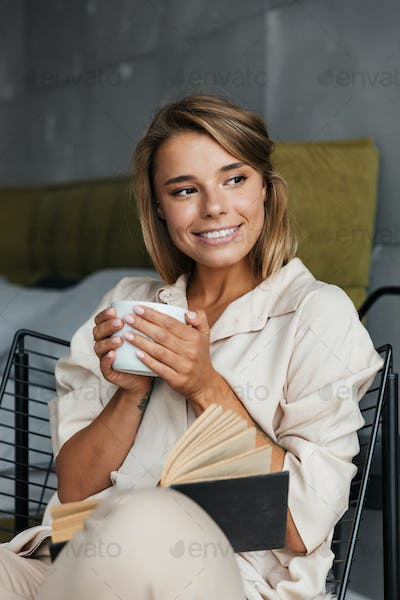 Image of woman drinking tea and reading book while sitting on armchair