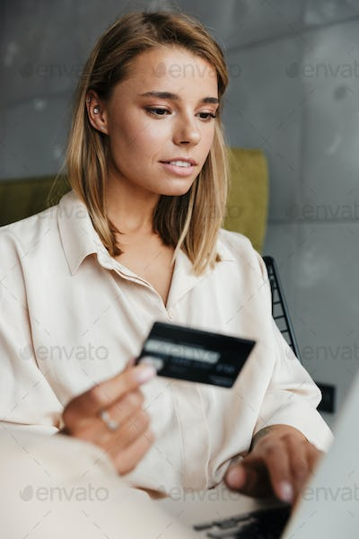 Image of focused nice woman holding credit card and using laptop